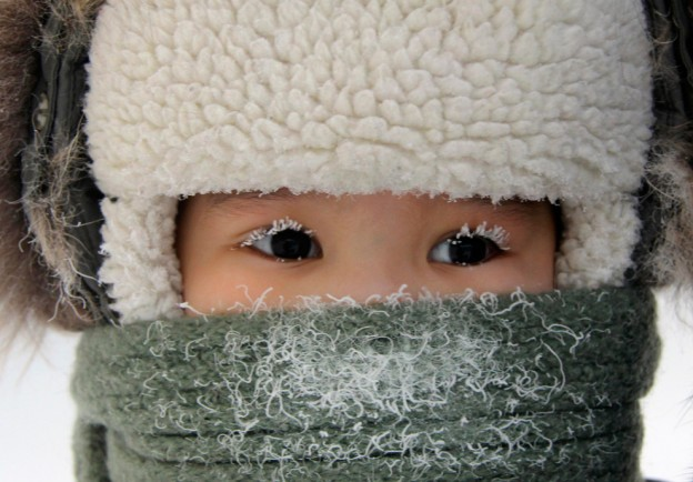 A child, with eyelashes covered with hoarfrost, along a street in the eastern Siberian city of Yakutsk in Sakha (Yakutia) Republic, Feb. 10, 2012. The air temperature in Yakutsk is about minus 35 degrees Celsius (minus 31 degrees Fahrenheit). (Viktor Everstov/Reuters)#